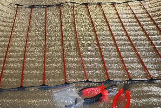 Стержневой теплый пол выполнен из гибких нагревательных элементов (стержней), соединенных между собой токопроводящими шинами