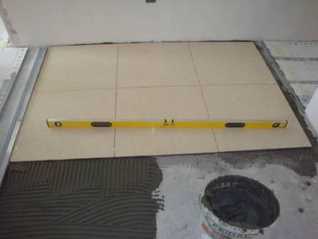 Перед укладкой плитки поверхность пола выравнивают по горизонтальному уровню