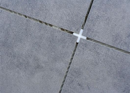 Чтобы швы были одинаковыми, между плитками вставляются крестики необходимой толщины