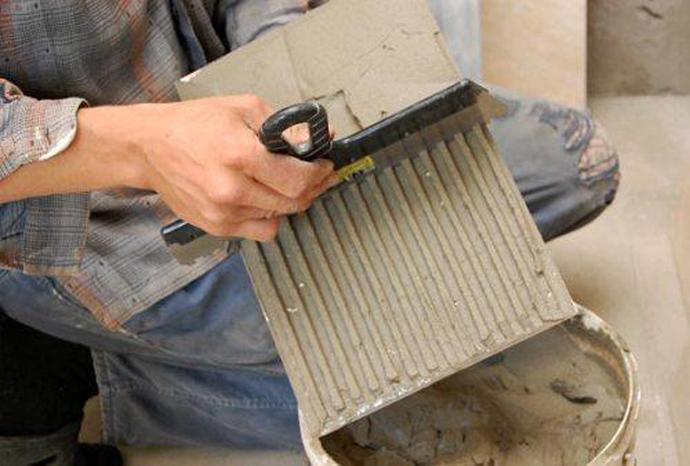 Шпатель нужно держать без наклона, перпендикулярно к плитке – так обеспечивается оптимальное количество нанесения клея
