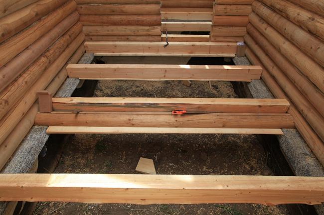 Лаги могут крепиться на стенки сруба или быть установленными на фундамент дома
